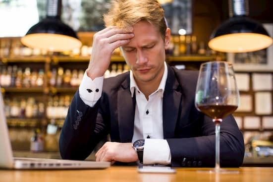 businessman having headache of drinking wine