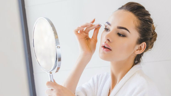 girl doing eyebrows in front of mirror