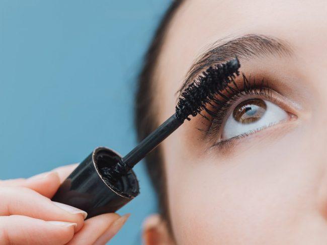 woman-applying-mascara-on-her-lashes-eye-envy