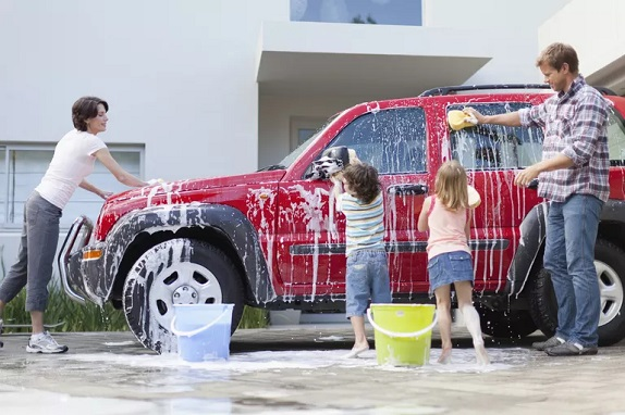 picture of family washing a big red car