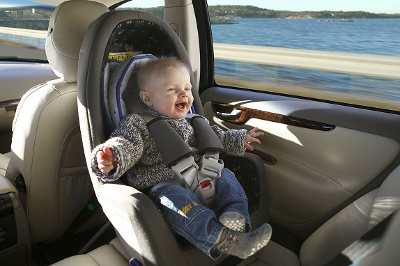 picture of a happy baby sitting in a rear-facing car seat while car is moving