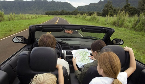 picture of family in a car travelling beside grass fields and mountains
