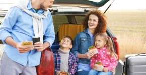 picture of a family around the car beside their luggage with sandwiches in their hands