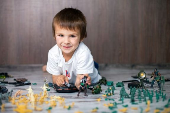 Cute little toddler boy, playing at home with soldiers and figur