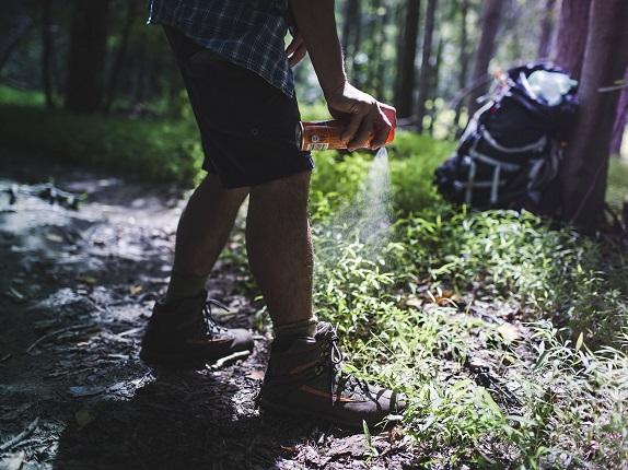man spraying for bugs while camping
