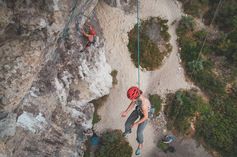 woman being lowered by rope after rock climbing