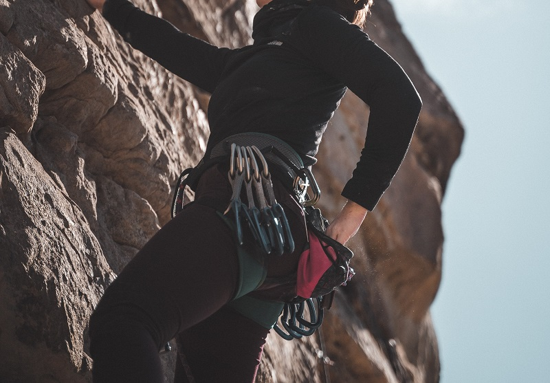 woman climbing with quickdraws