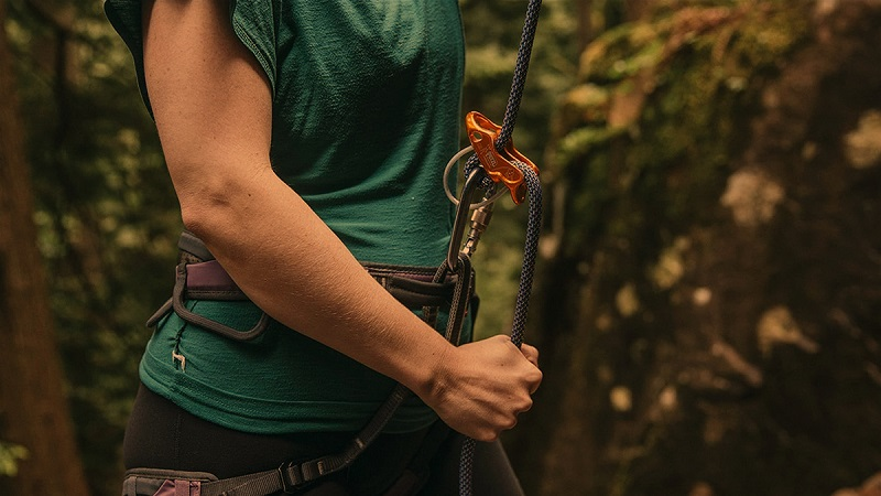 man putting on a belay devise on rope