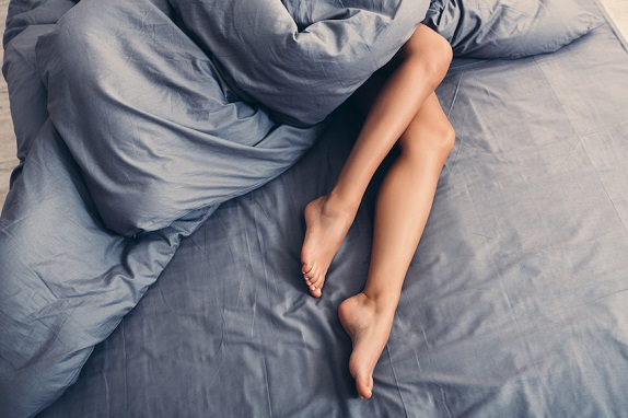 perfect legs of sleeping woman in bed